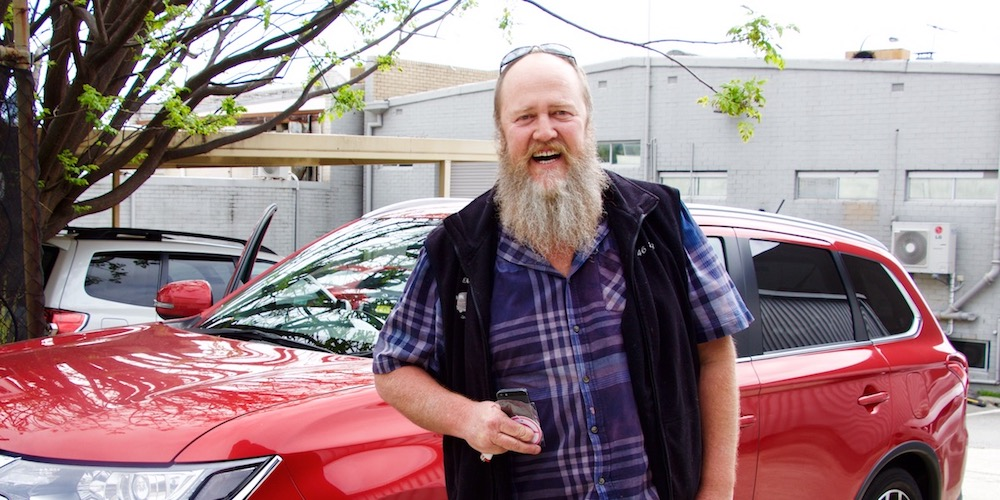 man with beard in front of uber rental car